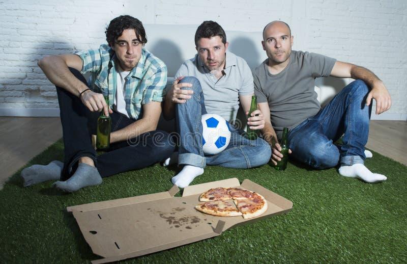 Os fan de futebol fanáticos dos amigos que olham a tevê combinam com o esforço do sofrimento das garrafas e da pizza de cerveja imagem de stock royalty free