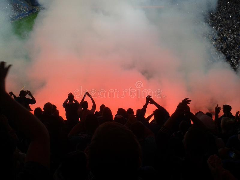 Os fan de futebol iluminaram acima as luzes e os alargamentos do fumo volta protesto fotografia de stock royalty free