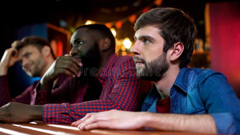 Os fan de futebol que olham o jogo no bar, os amigos masculinos decepcionados com equipe perdem foto de stock