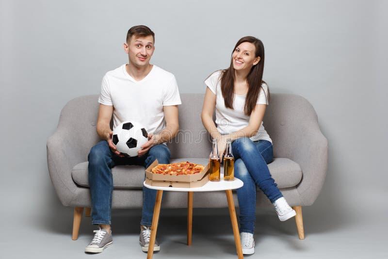 Os fan de futebol de sorriso do homem da mulher dos pares no elogio branco do t-shirt apoiam acima a equipe favorita com a bola d fotos de stock royalty free