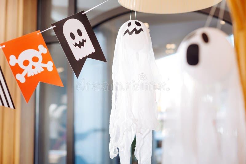 Os fantasmas assustadores e as bandeiras com os crânios que encontram-se como decorações para crianças de Dia das Bruxas party fotos de stock