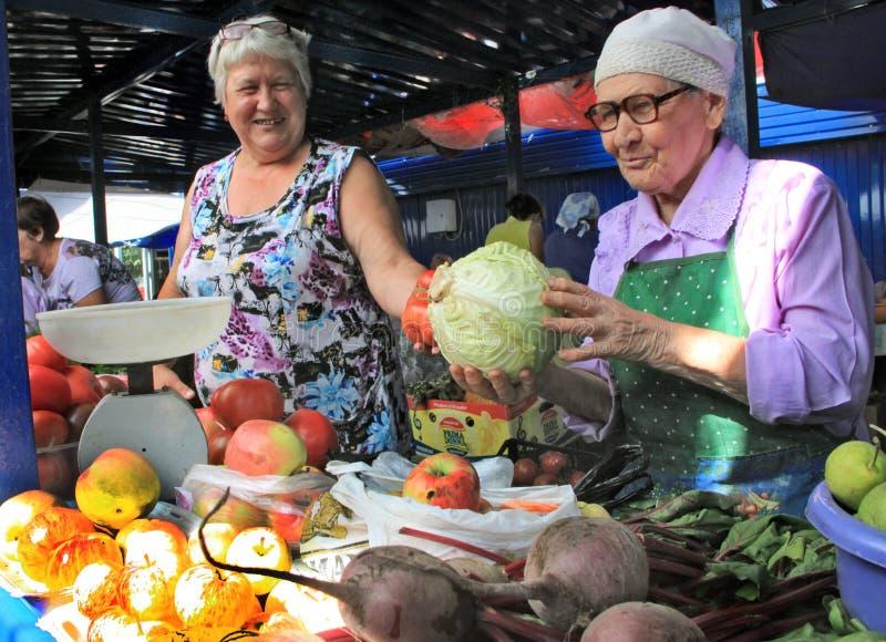 Os fazendeiros vendem seus produtos no mercado da exploração agrícola foto de stock
