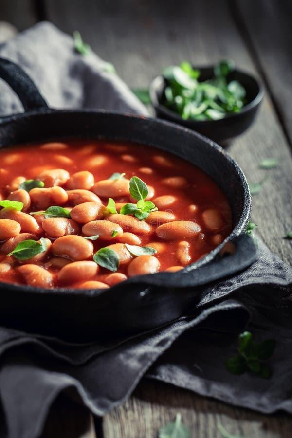 Os feijões cozidos saborosos fizeram de tomates e de ervas frescos fotos de stock