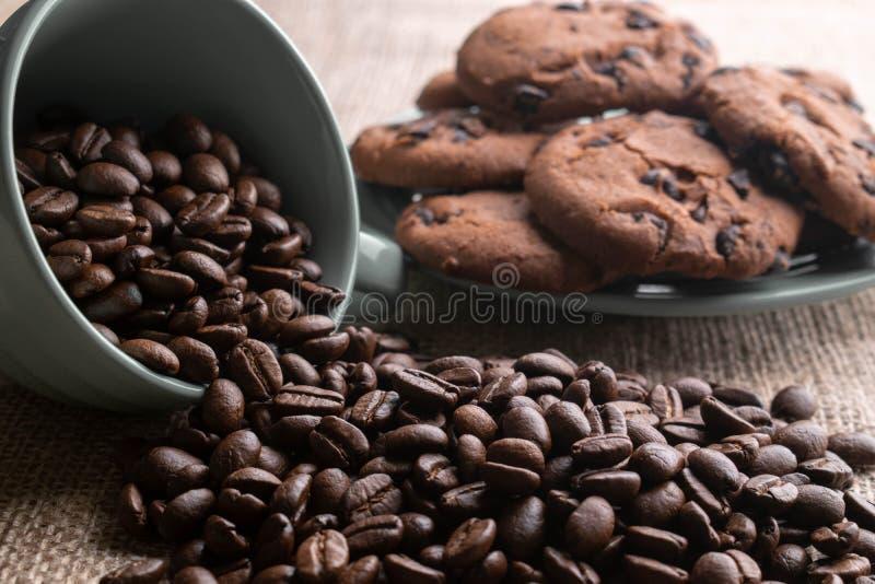 Os feijões de café desintegraram-se com um copo, no fundo uma placa das cookies imagem de stock