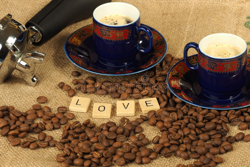 Os feijões de café, dois copos ornamentado e o punho do grupo com as letras amam em um fundo da juta fotografia de stock