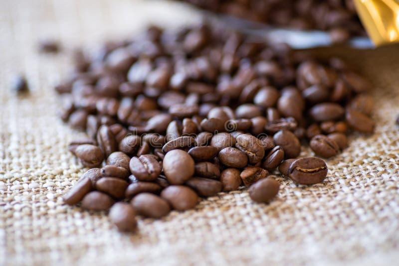 Os feijões de café marrons Roasted dispersaram o close-up, fundo, textura imagem de stock