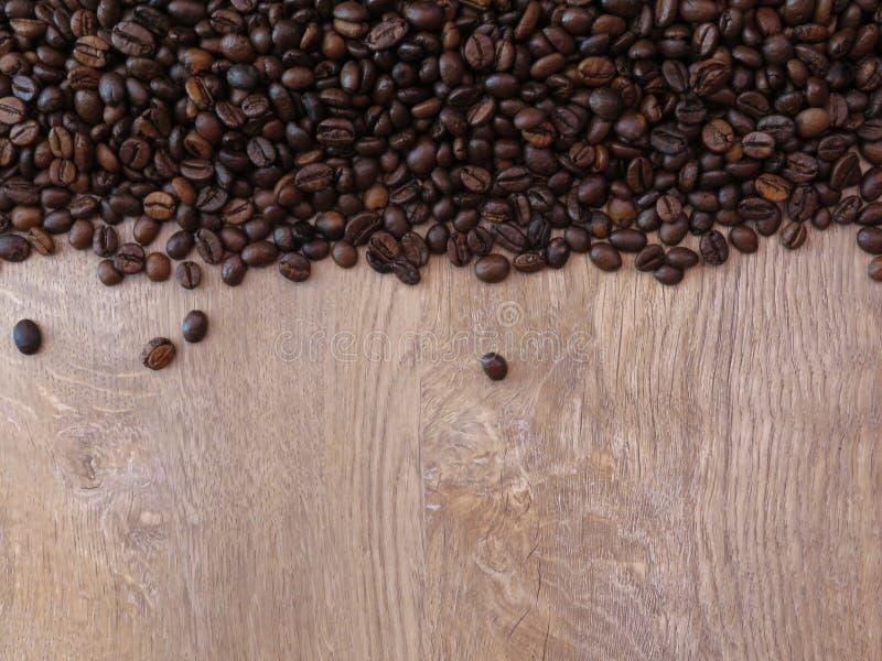 Os feijões de café na textura de madeira do carvalho fino modelam o fundo Espaço para o texto fotografia de stock