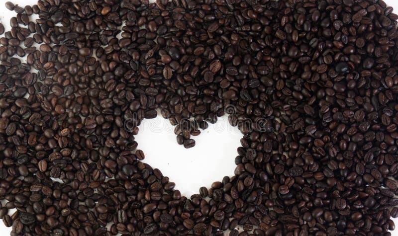 Os feijões de café no coração dão forma no fundo branco isolado foto de stock royalty free