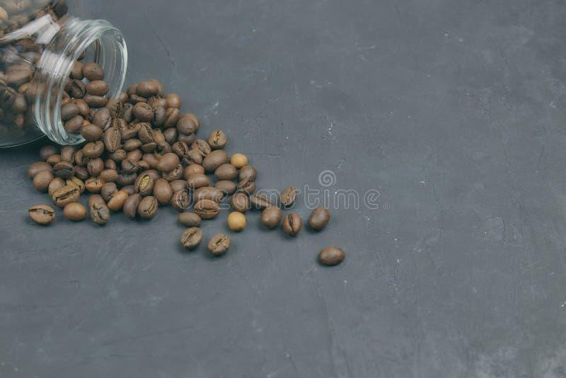 Os feijões de café Roasted derramaram de um frasco de vidro colocação angular do objeto do café no concreto escuro Vista horizont foto de stock royalty free