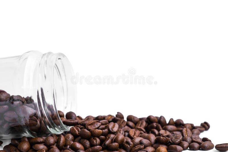Os feijões de café roasted frescos derramam do frasco de vidro imagem de stock royalty free