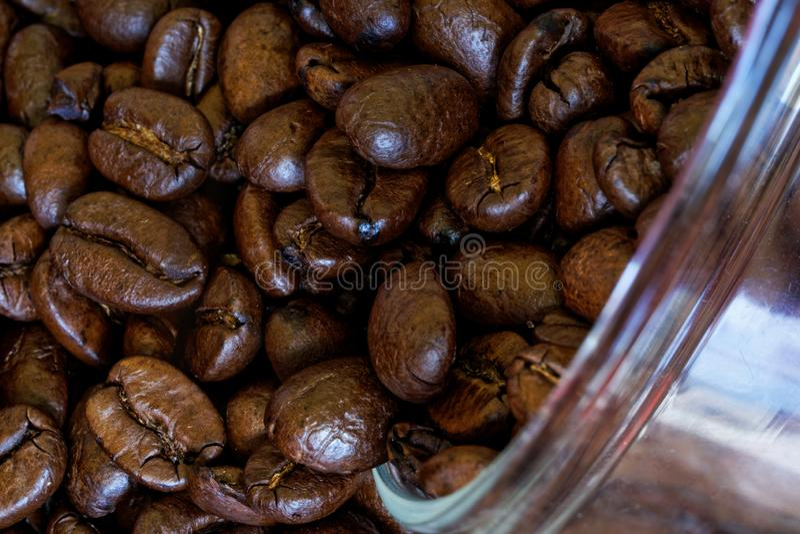 Os feijões de café Roasted são derramados fora de um frasco de vidro em uma planta de embalagem Close-up Macro fotografia de stock royalty free