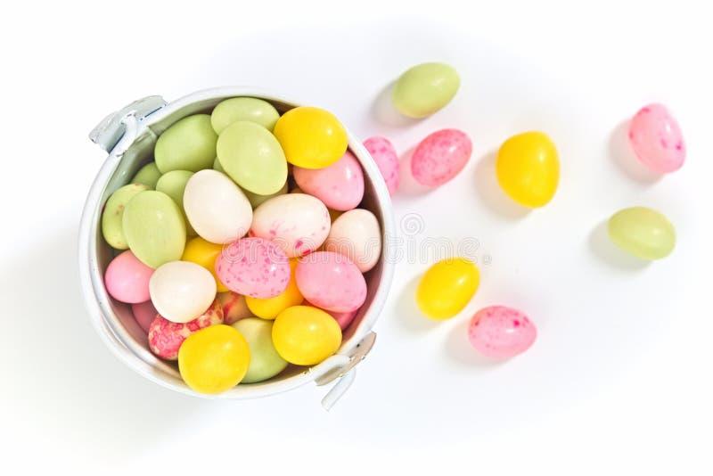 Os feijões de geleia da cor pastel egg a forma para doces de easter na cubeta branca foto de stock