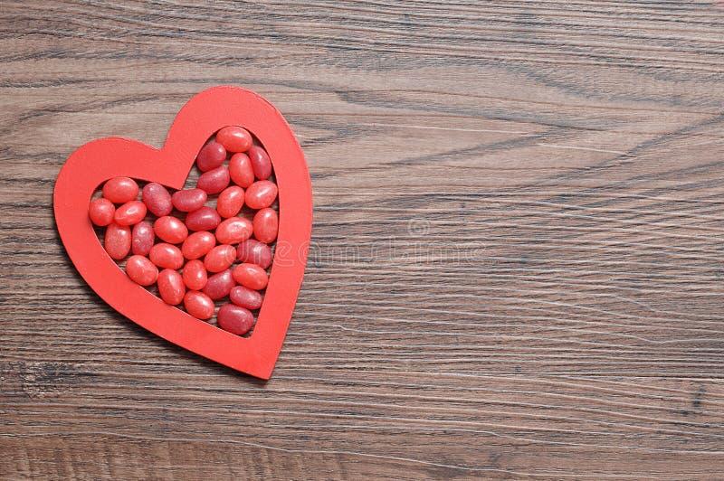 Os feijões de geleia vermelhos indicados em um coração vermelho dão forma fotografia de stock