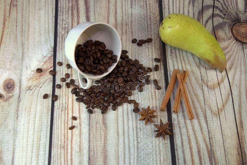 Os feijões invertidos de uma xícara de café, uma pera verde madura, um grupo da canela e os anisets da estrela encontram-se em um imagem de stock