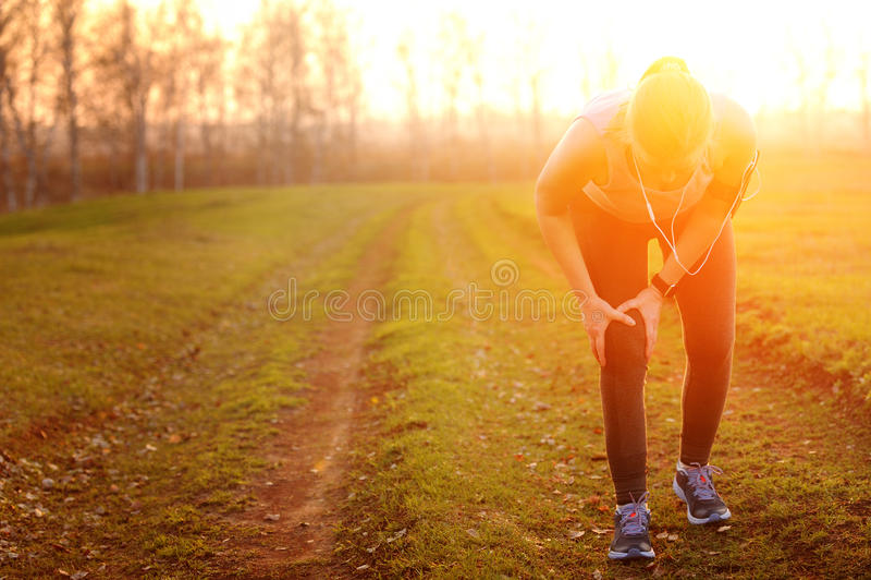Os ferimentos - esportes que correm a lesão de joelho na mulher fotos de stock