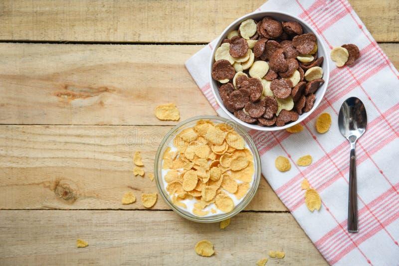 Os flocos de milho tomam o pequeno almoço e o copo do leite da bacia de vários cereais no fundo de madeira da tabela para o ali fotografia de stock royalty free
