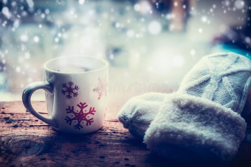 Os flocos de neve agridem com bebida quente e os mitenes de confecção de malhas no peitoril da janela da geada na natureza da nev imagens de stock