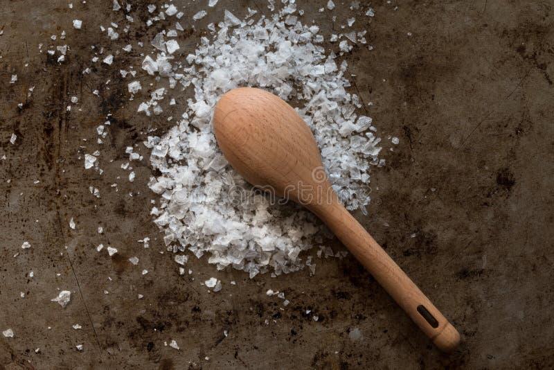 Os flocos de sal do mar derramaram a colher de madeira fotografia de stock royalty free