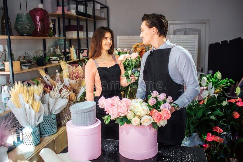 Os floristas novos alegres e agradáveis estão na sala e no olhar em se Sorriem Rosas brancas da posse fêmea do florista guy imagens de stock