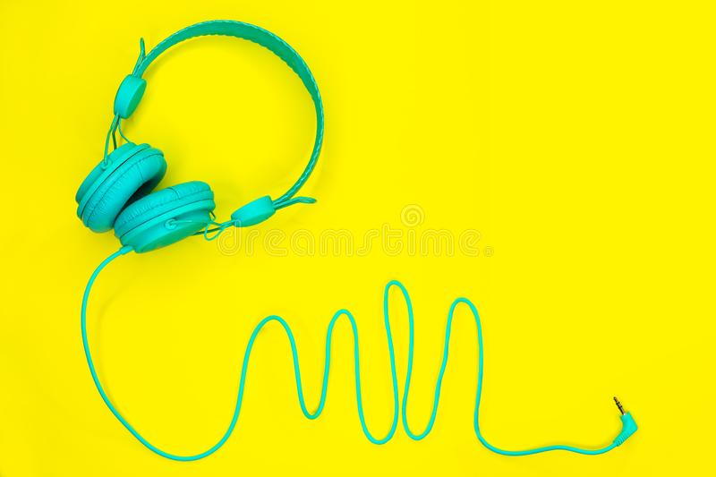 Os fones de ouvido azuis encontram-se em um fundo amarelo colorido com espaço da cópia foto de stock