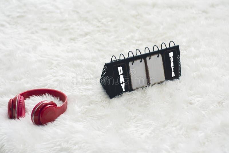 Os fones de ouvido e os calendários vermelhos do metal, são colocados em um tapete branco com o conceito do dia e do abrandamento foto de stock