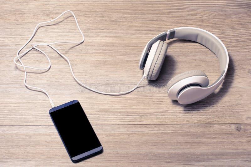 Os fones de ouvido e o telefone celular brancos em uma música de tabela escutam passatempo que dos fones de ouvido do amante o re fotos de stock