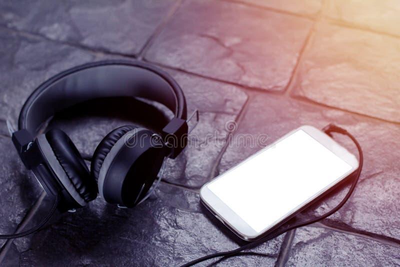 Os fones de ouvido pretos, com telefone celular escutam a música, o espaço branco seu texto fotos de stock