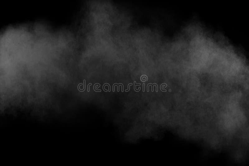 Os formul?rios estranhos da explos?o branca do p? nublam-se contra o fundo preto Respingo branco das part?culas de poeira imagens de stock