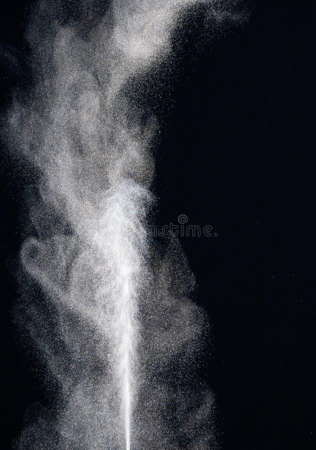 Os formul?rios estranhos da explos?o branca do p? nublam-se contra o fundo preto Respingo branco das part?culas de poeira foto de stock