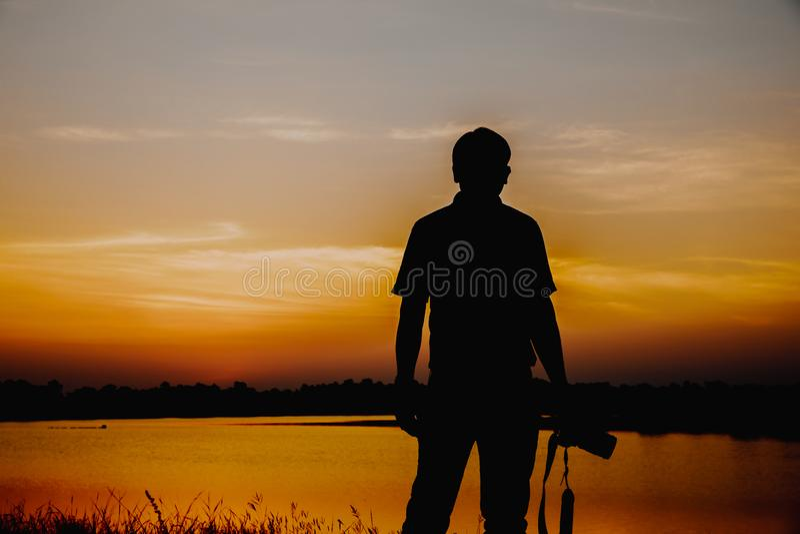 Os fotógrafo da fotografia do por do sol estão prontos para tomar uma foto do por do sol no reservatório Fotografia profissional fotografia de stock royalty free
