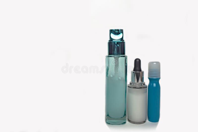 Os frascos de vidro para o cosmético desnatam em um fundo branco imagem de stock