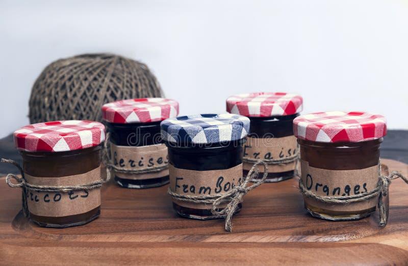 Os frascos de vidro pequenos com tampas frutificam ou doce da baga imagem de stock royalty free