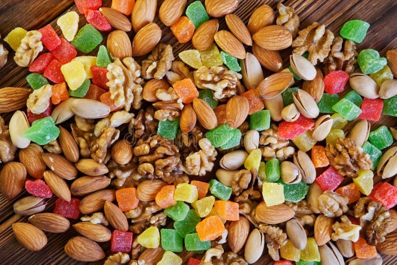 Os frutos cristalizados, os pistaches, as amêndoas e as nozes encontram-se em uma tabela de madeira rústica feita de pranchas do  fotografia de stock