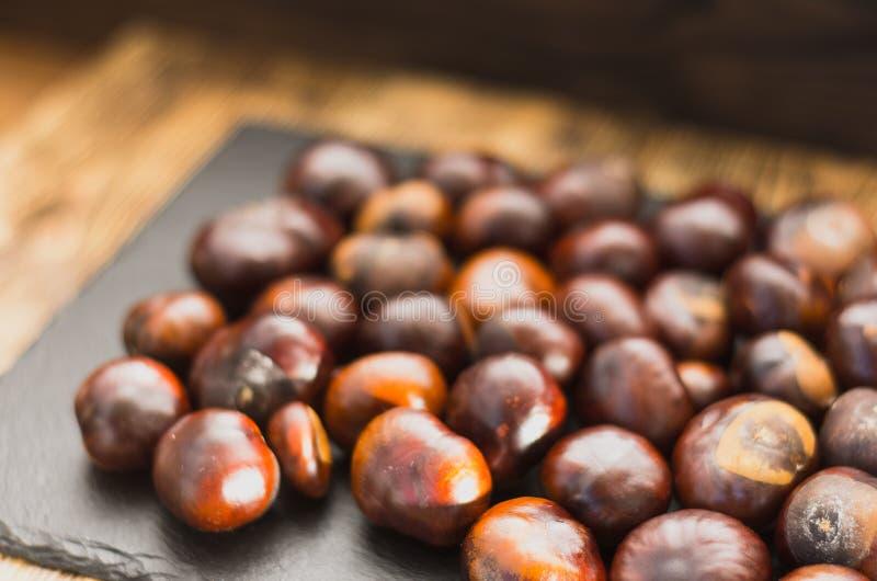 Os frutos da castanha são ficados situados em um prato da ardósia que encontra-se em um foco macio da tabela de madeira fotos de stock
