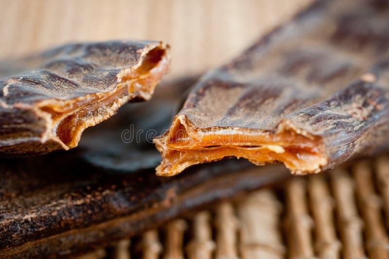 Os frutos e a alfarroba semeiam o close-up tomado na perspectiva de uma esteira de bambu imagem de stock royalty free