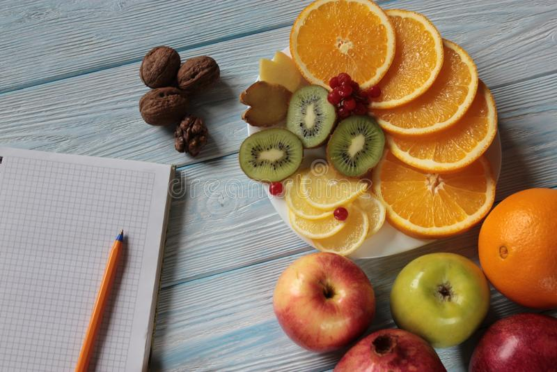 Os frutos encontram-se em um placa-quivi, em laranjas, em lim?o, em rom? e em comprimidos imagens de stock royalty free