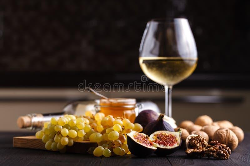 Os frutos inteiros frescos suculentos e um do figo cortaram figos e bacia de mel fotografia de stock