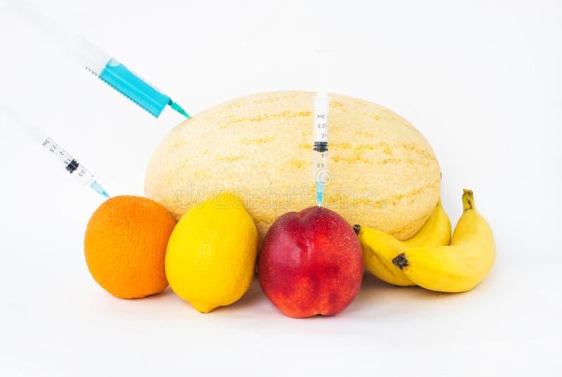 Os frutos nas bananas, na laranja, no melão, no limão e na nectarina de um fundo do branco em que gmo e tratam são injetados da s foto de stock royalty free