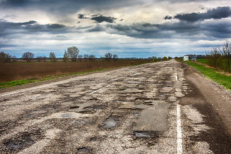 Os furos velhos dos caldeirões da estrada fora do outono da cidade resistem a HDR foto de stock