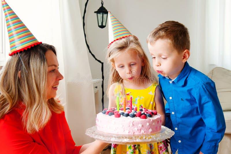 Os gêmeos bonitos da menina e do menino em chapéus do partido fundem para fora quatro velas em um bolo de aniversário A mamã sorr fotografia de stock