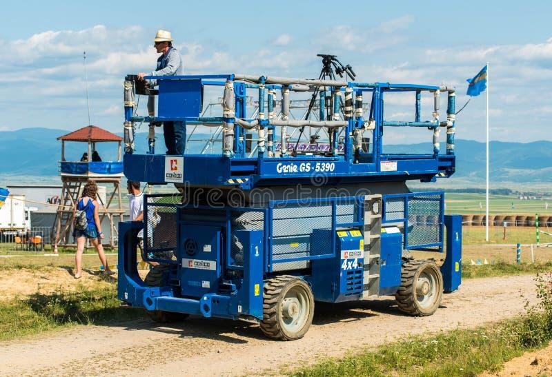 Os gênios GS 5390 automotores scissor o elevador usado para a transmissão de tevê viva na corrida de cavalos local imagens de stock royalty free
