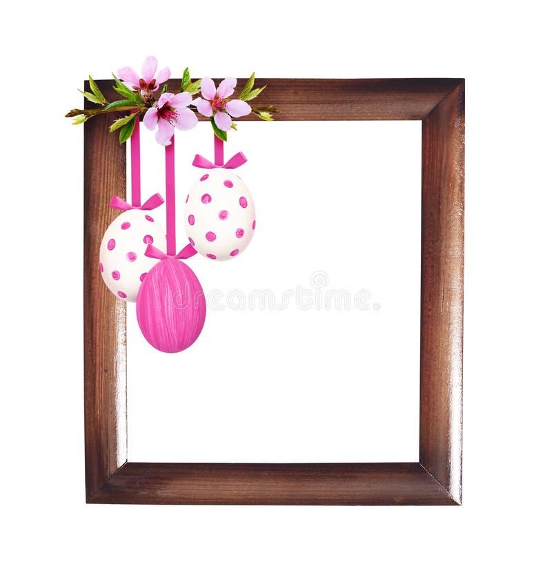 Os galhos da mola do pêssego florescem com ovos da páscoa e quadro de madeira fotografia de stock royalty free