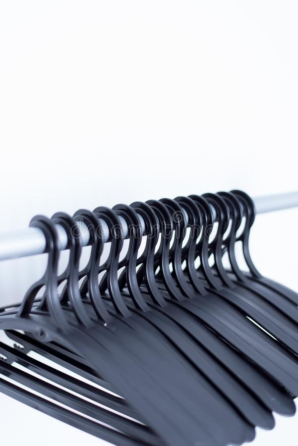 os ganchos plásticos pretos penduram em um fundo claro muitos ganchos diferentes foto de stock royalty free