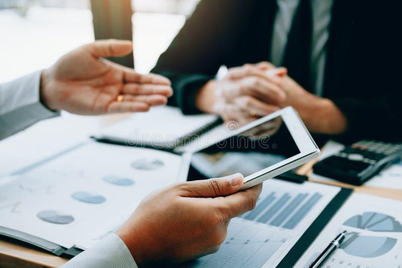 Os gerentes estão usando a tabuleta e explicam o relatório sumário ao empregado na sala do escritório fotos de stock