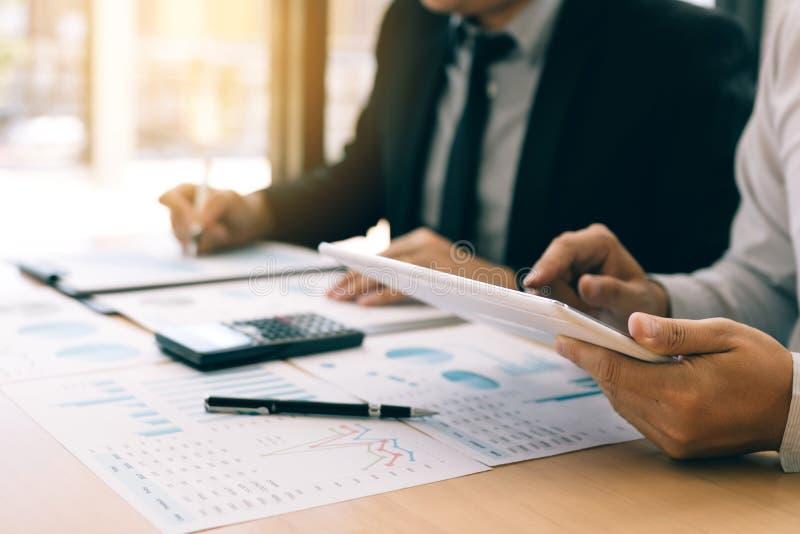 Os gerentes estão usando tabuletas para analisar vendas para custar relatórios e para explicar relatórios sumários aos empregados foto de stock