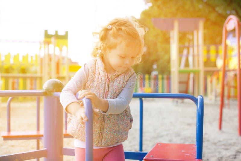 Os giros bonitos da menina no alegre vão círculo no parque das crianças no tempo ensolarado morno fotografia de stock royalty free