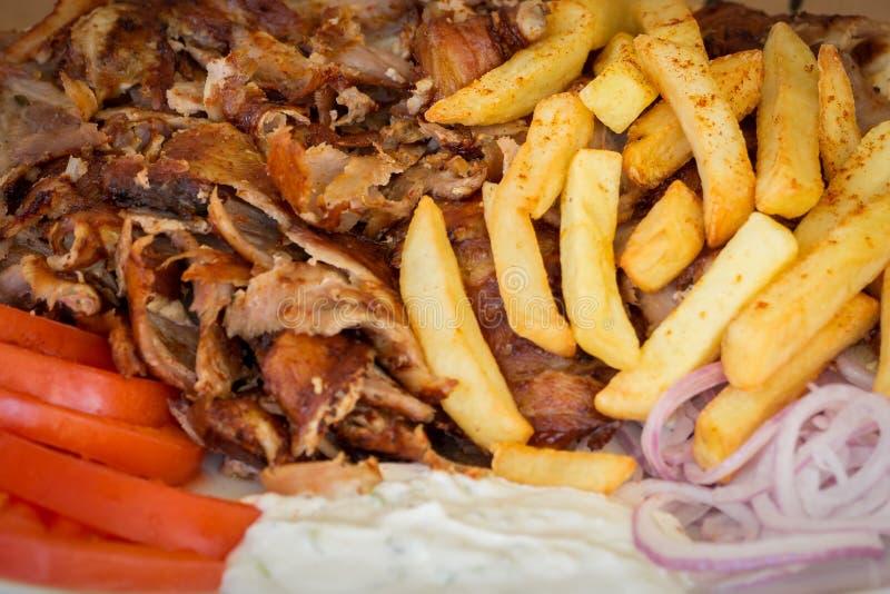Os giroscópios gregos, souvlaki, carne, fritaram batatas, tomates e cebolas, Atenas Grécia, alimento nacional, culinária grega tr fotografia de stock royalty free