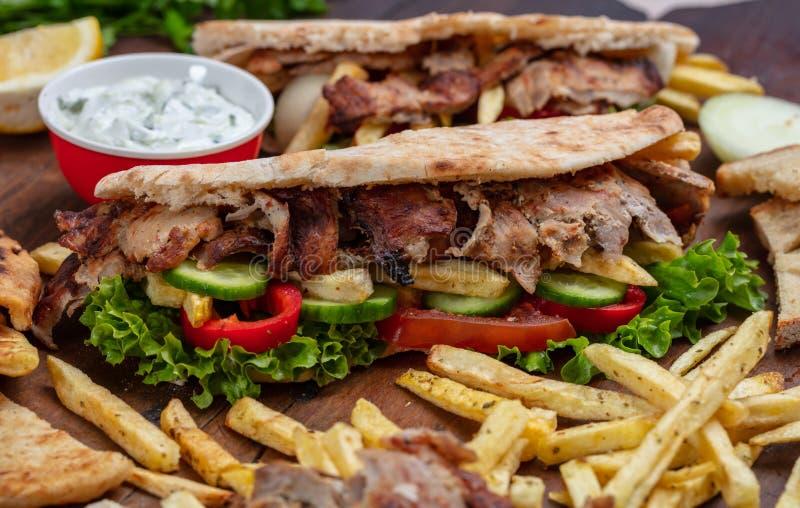 Os giroscópios, shawarma, levam embora, alimento da rua Sanduíche com carne na tabela de madeira fotos de stock royalty free
