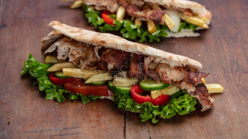 Os giroscópios, shawarma, levam embora, alimento da rua Sanduíche com carne na tabela de madeira imagens de stock