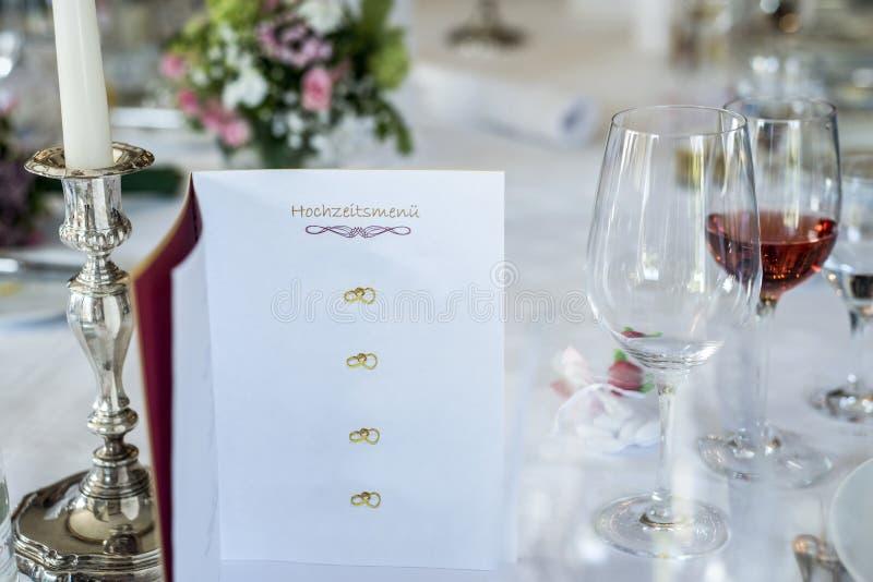 Os glas do vinho de tabela do jantar candle o menu alemão Copyspace do casamento da tradução do hochzeitsmenu do texto do encabeç imagem de stock royalty free